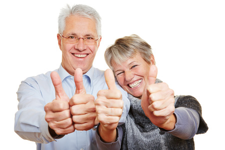 Happy elderly senior couple holding their thumbs up photo