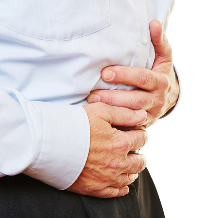 Elderly man with bellyache holding stomach with his hand photo