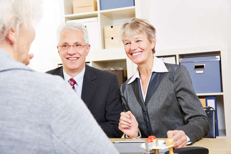 Two elderly business people talking about finances with senior woman Stock Photo - 27497346