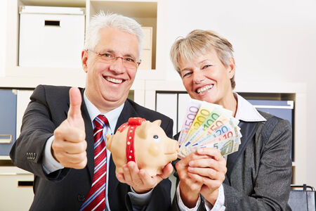 Two happy senior people with money and piggy bank holding thumb up Stock Photo - 27497352