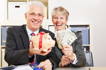 Two elderly happy business people with fan of dollar bills and piggy bank Stock Photo - 27497354