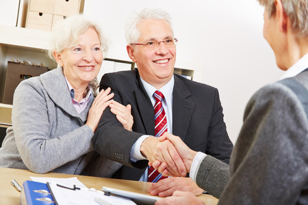 Senior couple giving handshake to consultant for a greeting photo