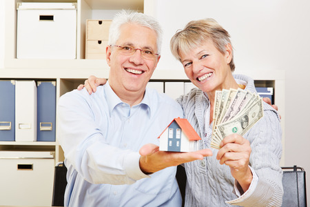 Happy elderly senior couple with small house and fan of dollar bills photo