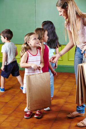 maestra jardinera: Maestra de Kindergarten dando bolsas con regalos a un grupo de ni�os