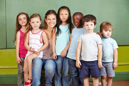 nourrisson: Heureux groupe d'enfants de sourire enseignante de maternelle dans une pi�ce Banque d'images