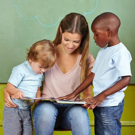 maestra jardinera: Ni�os y maestra de kinder leyendo juntos en un libro