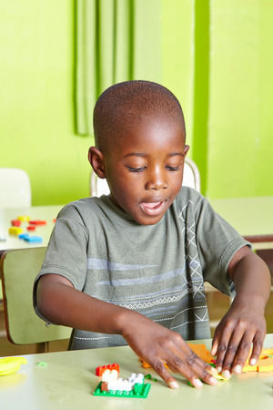 Happy african child playing in kindergarten with building blocks photo