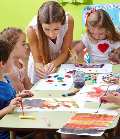 Nursery teacher painting with children and brushes and watercolor in kindergarten photo
