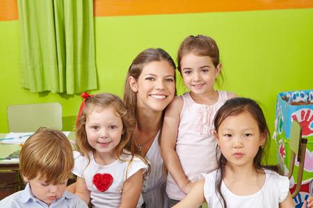 day care center: Portrait of children with happy nursery teacher in a kindergarten Stock Photo