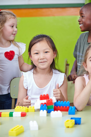Chinese child in kindergarten holding her thumbs up while playing photo