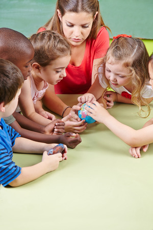 kid smiling: Kids learning geography in kindergarten with a little globe Stock Photo