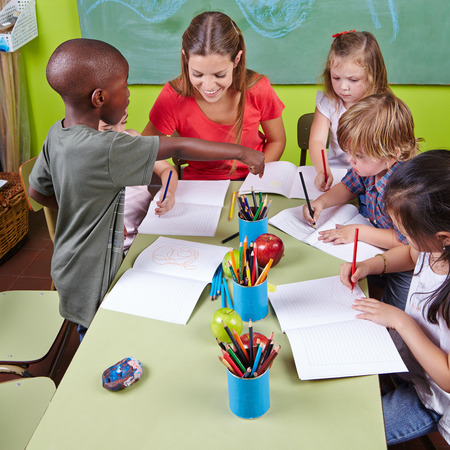 Interracial group of children drawing with nursery teacher in kindergarten