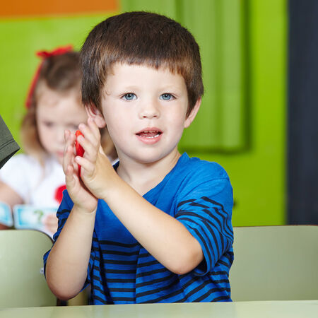 little dough: Child at table playing with dough in a kindergarten Stock Photo