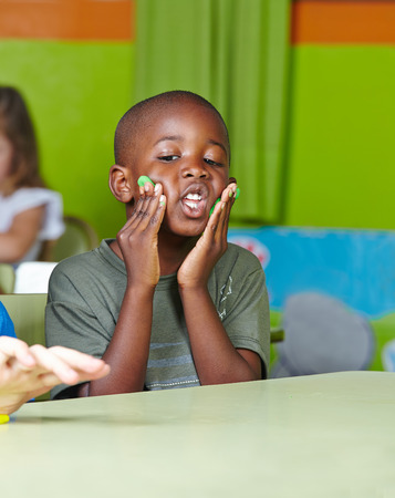 Unsinn: Dumme afrikanisches Kind machen Unsinn mit Teig in einem Kindergarten