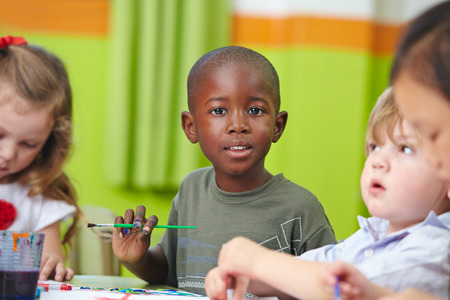 Muchos niños en la pintura preescolar junto con pinceles y colores