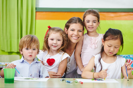 day care center: Portrait of a happy nursery woman and children together in a kindergarten Stock Photo