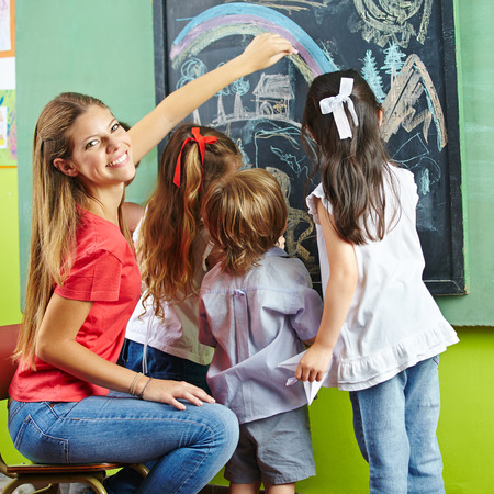 Nursery teacher and children painting a picture on chalkboard in a kindergarten