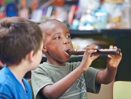 flauta dulce: Niño africano que toca la flauta en una escuela de música Foto de archivo