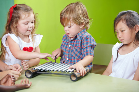xylophone: Boy playing xylophone in kindergarten at musical education Stock Photo