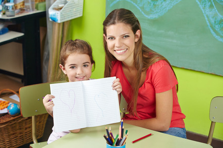 Proud child showing drawing in kindergarten with nursery teacher Stock Photo