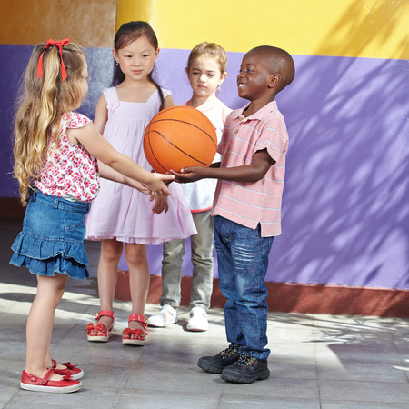 Interracial group of children playing together with basketball in kindergarten Stok Fotoğraf - 27574819