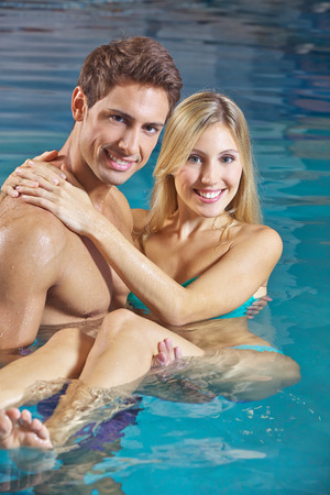 woman in bath: Happy man carrying smiling woman in a swimming pool