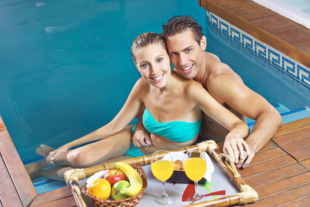 Smiling couple eating breakfast with fruits and juice in a swimming pool photo