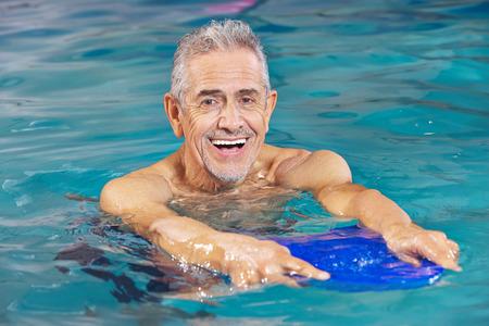 swim: Hombre mayor feliz con una tabla flotadora en el agua de la piscina