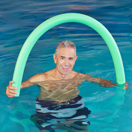 physiotherapy: Old man in swimming pool doing aqua fitness with swim noodle Stock Photo