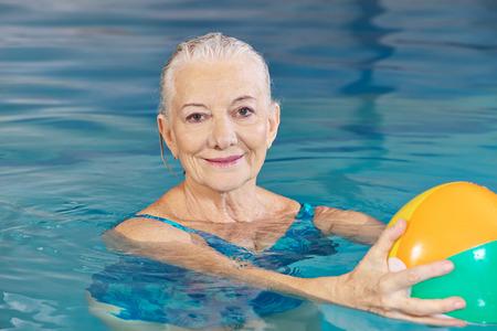 Gelukkig senior vrouw met water bal in het zwembad doen aquafitness