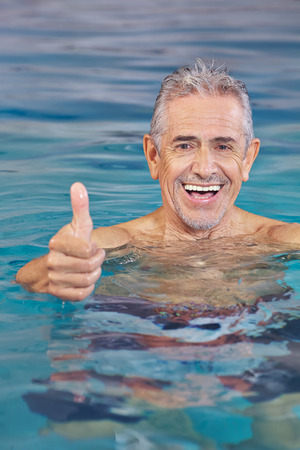 Happy old man in swimming pool holding his thumbs up photo