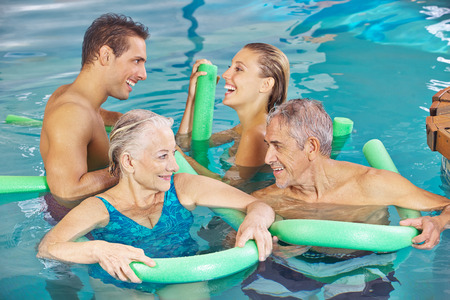 Happy group in swimming pool doing aqua fitness with swim noodles photo