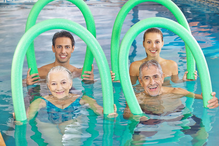 Group of senior people with swim noodles in a swimming pool photo