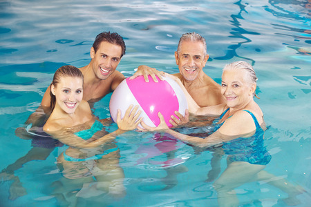 Happy group playing in swimming pool with a water ball in summer photo
