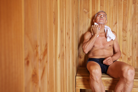 Old man with towel relaxing in sauna of a hotel Stock Photo
