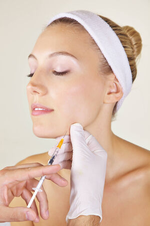 Woman in beauty clinic getting cosmetic surgery with syringe photo