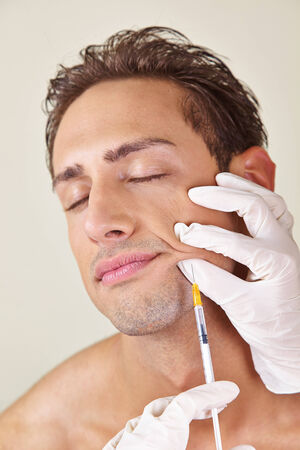 Man getting syringe with hyaluronic acid against wrinkles in the mouth area photo
