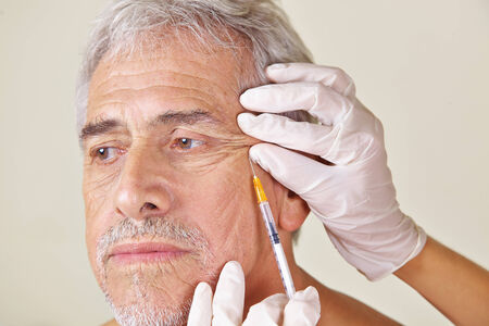 attractiveness: Old man getting wrinkles treatment against crows feet in beauty clinic Stock Photo