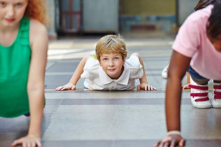 Niños haciendo flexiones en Educación Física en la escuela primaria