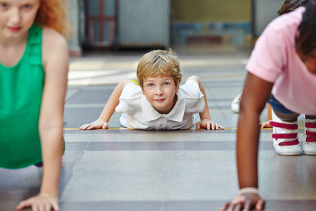 ni�os sonriendo: Ni�os haciendo flexiones en Educaci�n F�sica en la escuela primaria