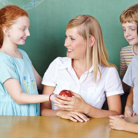 Student bringing teacher an apple in elementary school photo