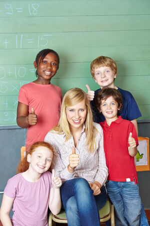 traineeship: Happy teacher and students holding thumbs up in elementary school