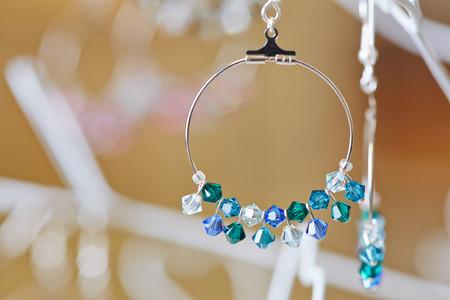 宝石店でディスプレイ上の宝石商から派手なイヤリング
