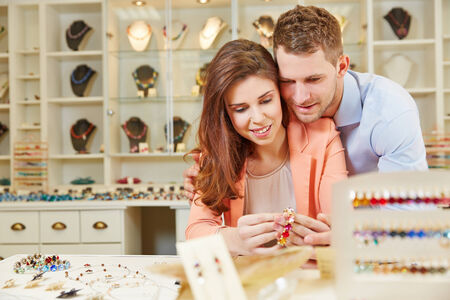 Happy couple buying together juwelry at a jeweler store photo