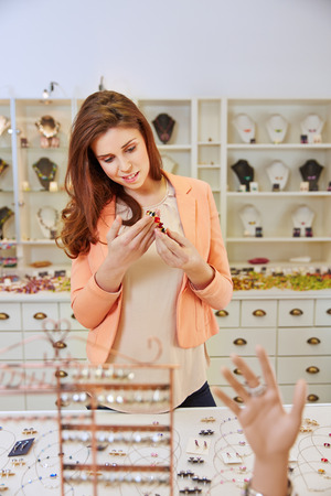 Woman shopping for bracelet and jewelry in a jeweler store photo