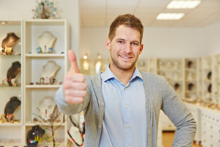 Smiling man in jewelry store holding his thumbs up Stock Photo - 28061753