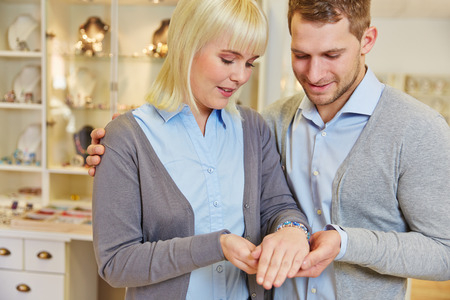 Happy couple shopping in jewelry store for a bracelet photo