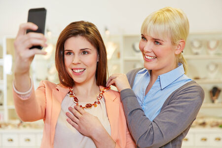 Woman taking selfie at jewelry store while trying on a necklace photo
