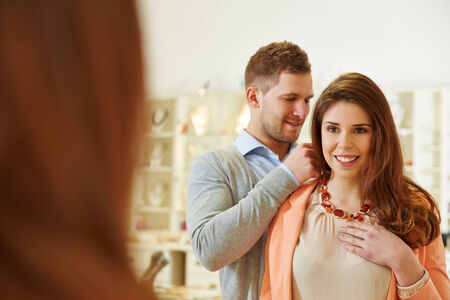 Man helping woman with fitting of a necklace at jeweler store photo