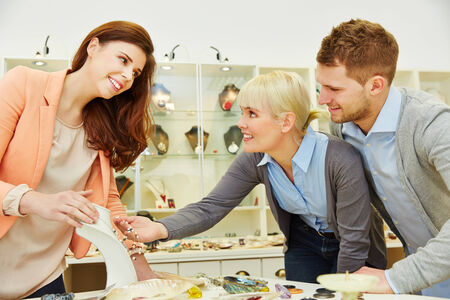 Smiling saleswoman advising two custormers in a jewelry store photo